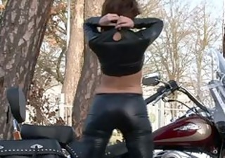 biker babe disrobes out of leather outfit on her
